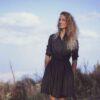 Момиче с черна къса рокля с колан. Модна фотоградия